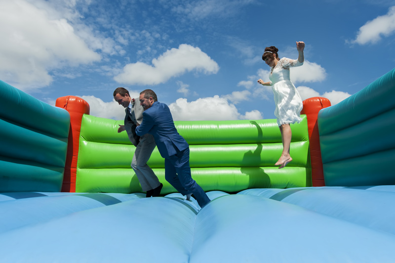 Couple on bouncy castle at Leeford place wedding by Sussex wedding photographer James Robertshaw