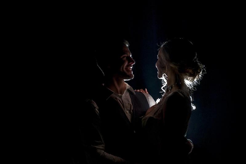 Newleyweds in the dark lit from behind