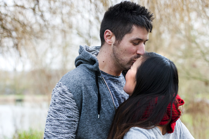 Man kissing fiancé forehead - natural couple photography by James Robertshaw