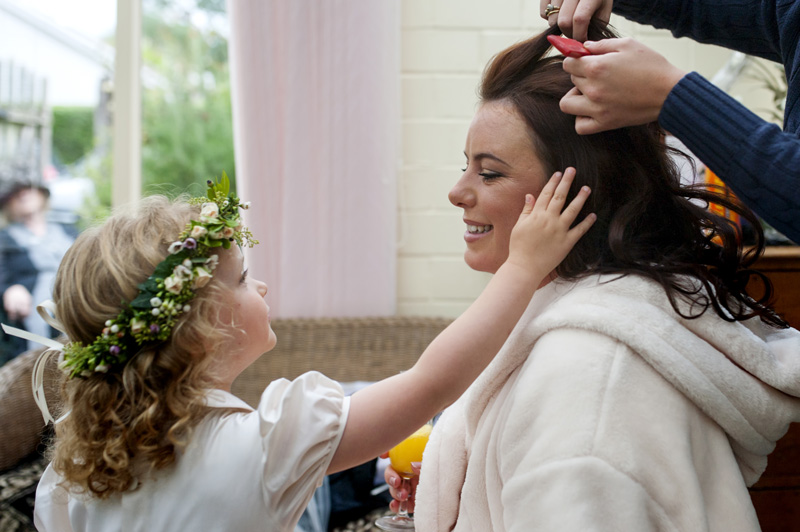 Bride smiling at flower girl while getting ready