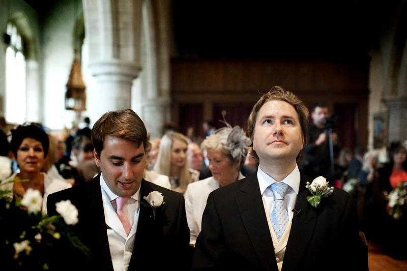 Groom looking up in church waiting for bride