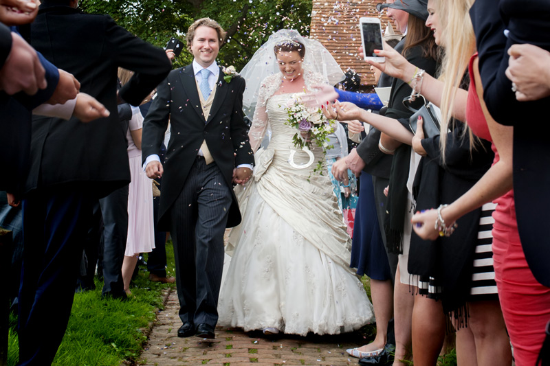 Bride and groom with confetti at East Sussex wedding