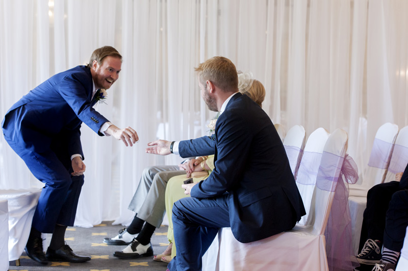 Groom handing ring to brother