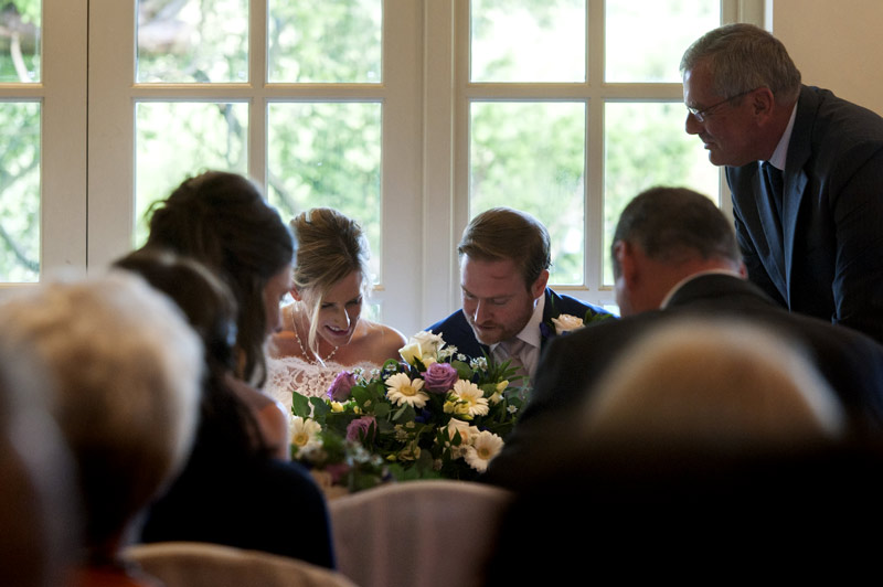 Bride and groom signing register Bannatynes Hotel Hastings wedding