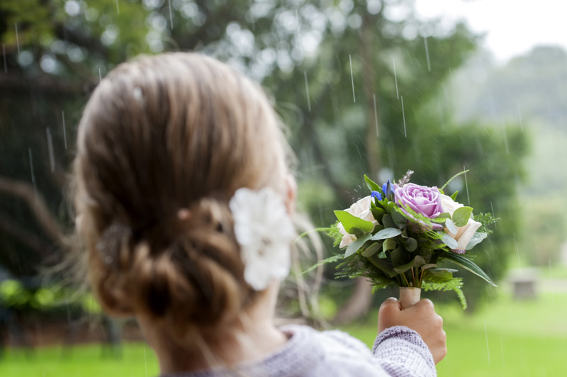Flower girl holding bouquet in the rain at Bannatynes Hotel Hastings wedding