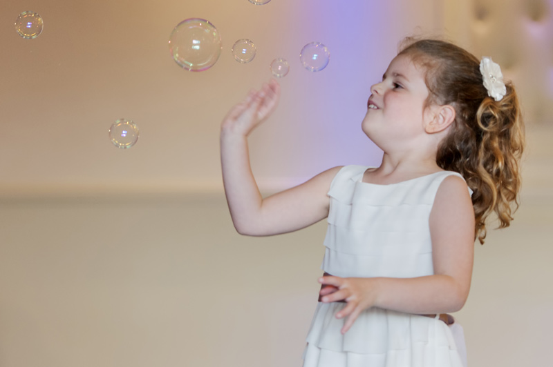 Girl playing with bubbles at wedding