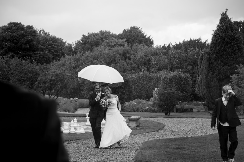 Bride and groom under umbrella at Bannatynes Hotel Hastings wedding