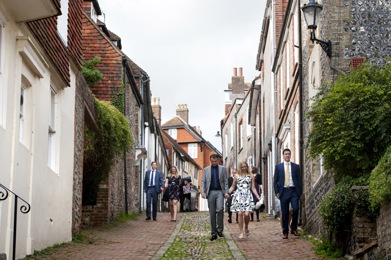 Wedding guests walking down Lewes cobbled street