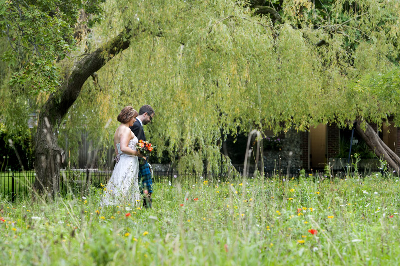 Bride and Groom walking through flowers
