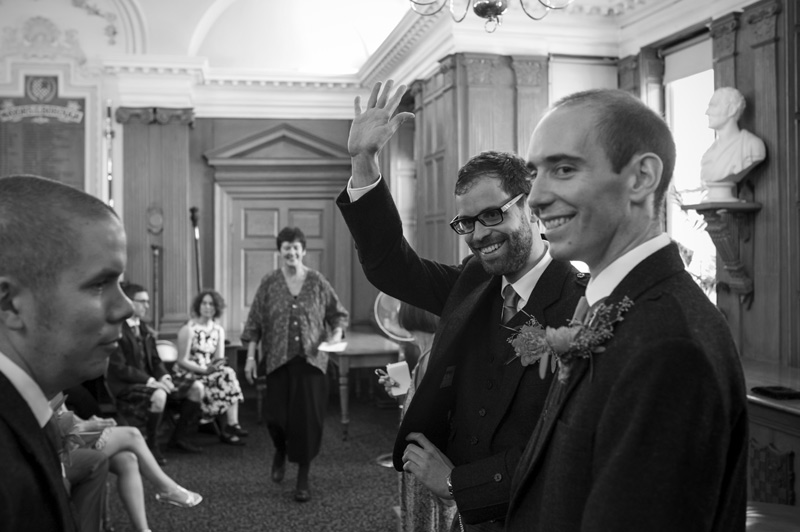 Groom waving before Lewes Town Hall wedding ceremony