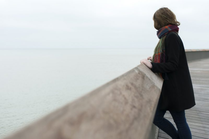 Hastings Pier photographs - Girl looking out to sea from Hastings Pier