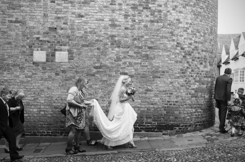 Bride walking through on cobbled street to Rye Town hall wedding