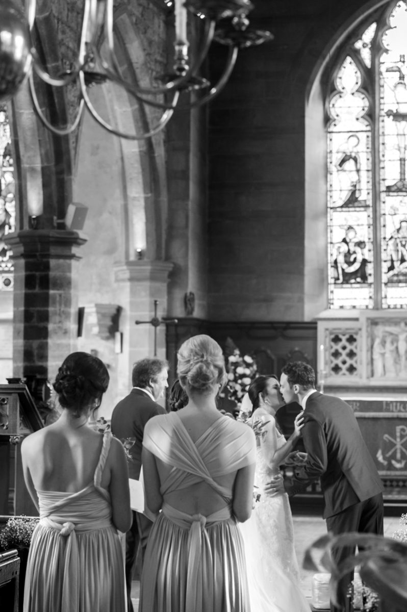 Bride and groom kiss at Chiddingstone church