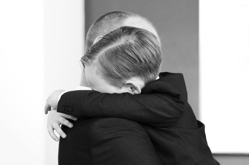 Father and son hugging at wedding