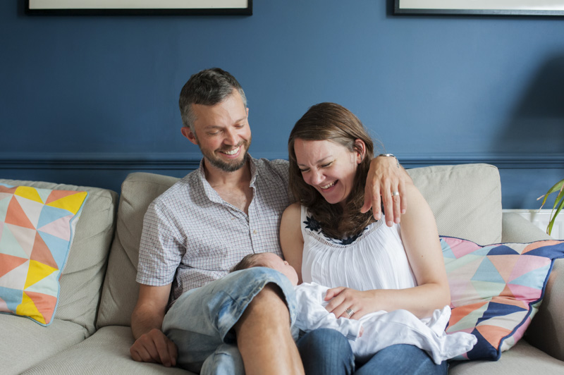 Couple laughing with baby by Sussex family photographer James Robertshaw