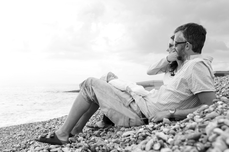 Young family sitting on Hove beach by Sussex family photographer James Robertshaw