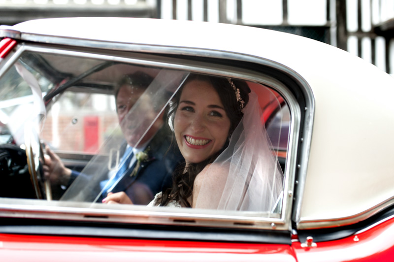 Plough at Leigh wedding - bride smiling with father in car
