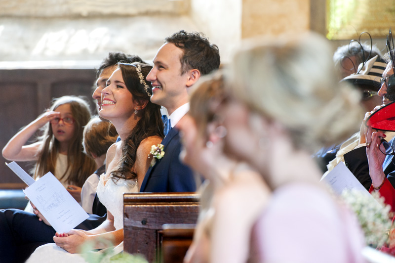 Plough at Leigh wedding - couple smiling watching reading in church