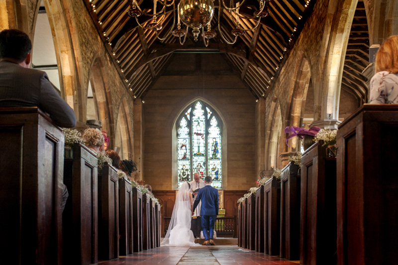 Plough at Leigh wedding - couple kneeling in church