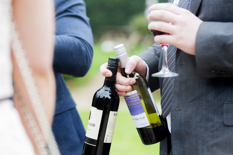 Close up of wedding guest holding two bottles of wine in one hand