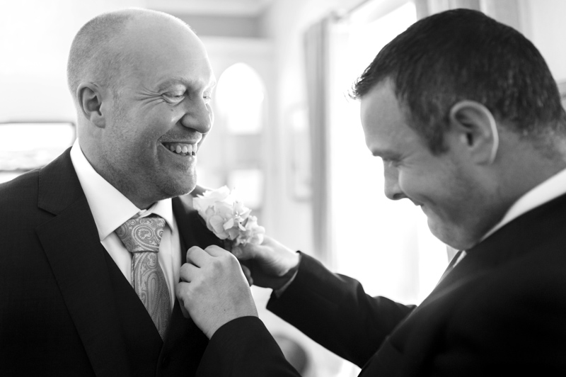 Crowhurst Park wedding - best man fixing groom's buttonhole
