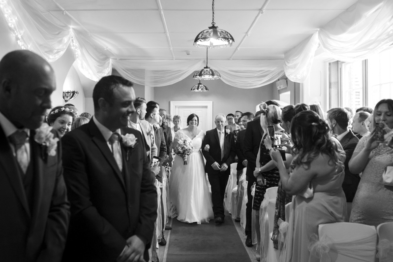 Crowhurst Park wedding - bride and father walking down the isle