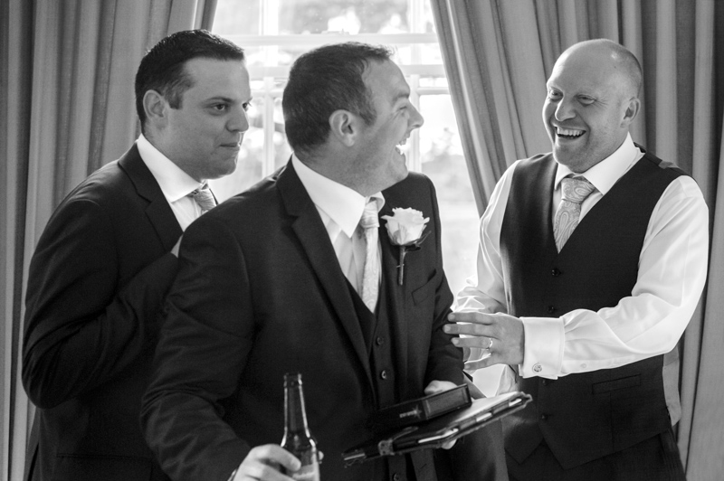 Crowhurst Park wedding - groom laughing