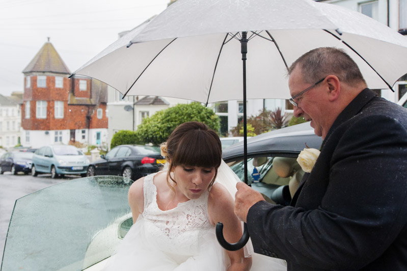 Bride alighting from car with father