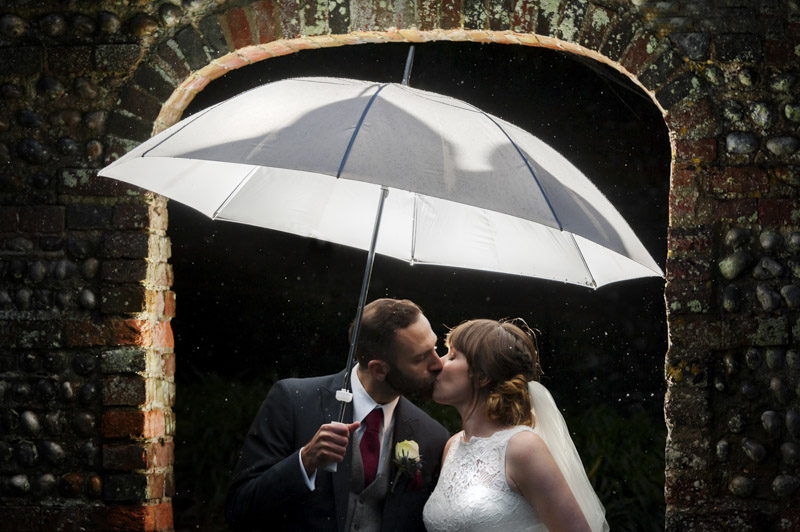 Manor Barn wedding - couple kissing in the rain