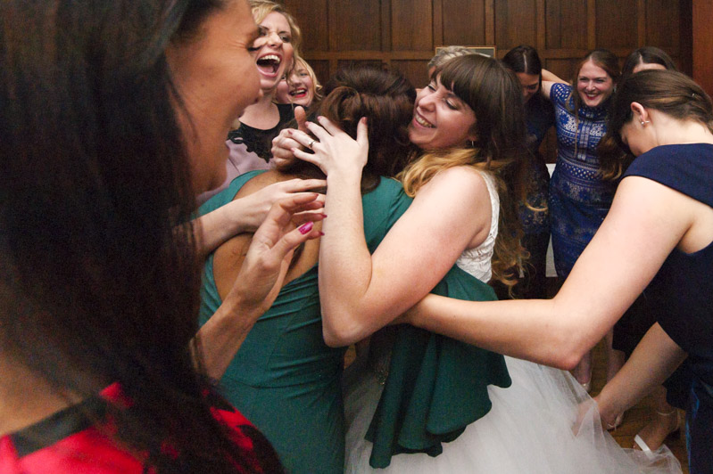 Bride embracing friends on the dance floor
