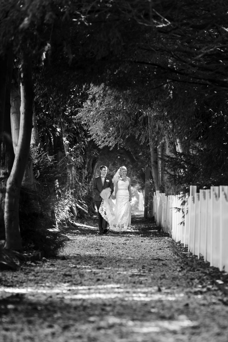 Bride and groom walking down path at Hayne House