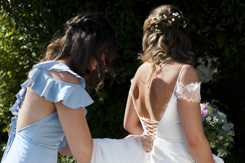 Bridesmaid tying bride's dress at Otham Court wedding