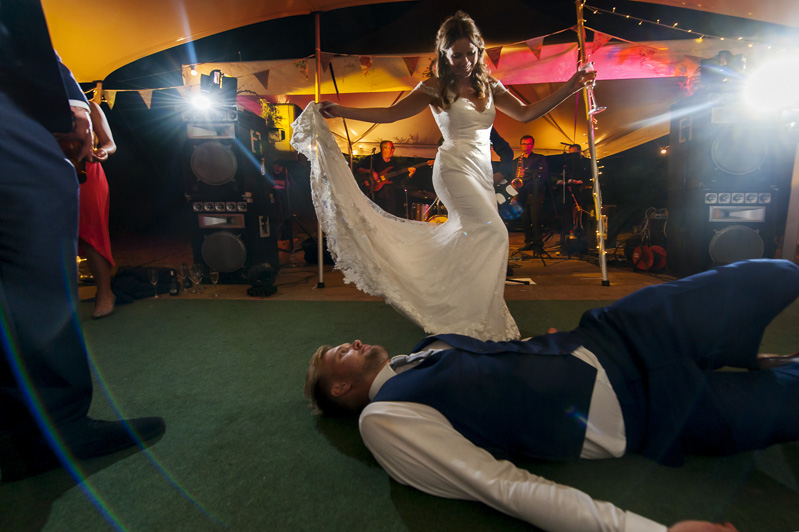 Groom lying on dancefloor in front of bride