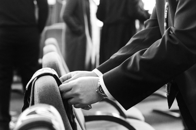 Placing a scarf on absent wedding guests seat - Hastings wedding photography