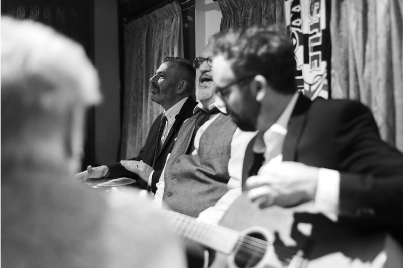 Groom and friends playing live music - Hastings wedding photography